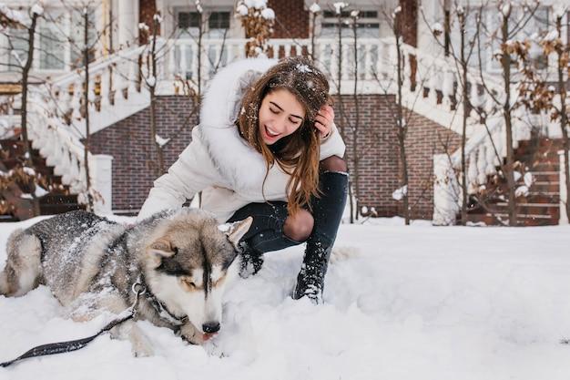 Enthousiaste vrouw met lichtbruin haar die haar husky puppy bekijkt en glimlacht. outdoor portret van zalige jonge vrouw poseren met hond op sneeuw.