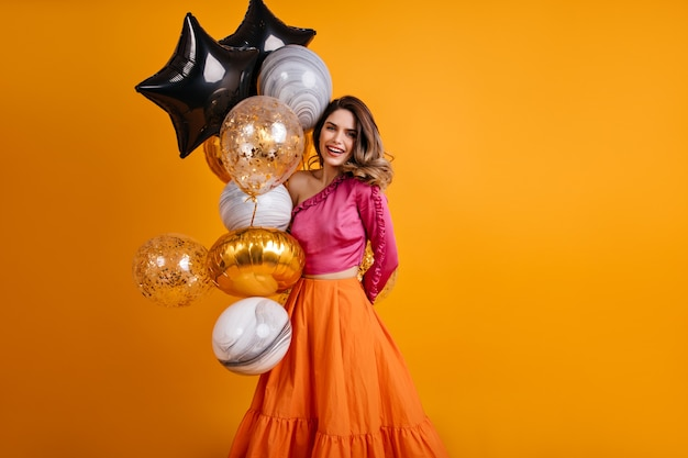 Enthousiaste vrouw poseren met ballonnen op haar verjaardag