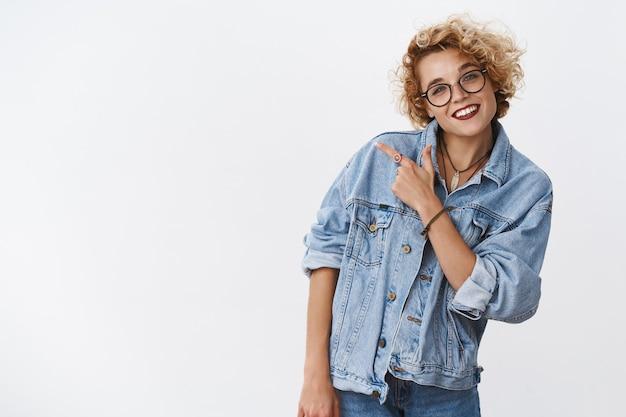 Enthousiaste vrouw verwelkomt ons terwijl ze naar de linkerbovenhoek wijst om geweldige advertenties te tonen die breed glimlachen en het hoofd kantelen, vreugdevol verzekerd dat we van promotie houden die tegen een grijze muur staat