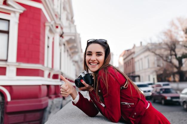 Enthousiaste vrouwelijke fotograaf met rode manicure ontspannen in het weekend