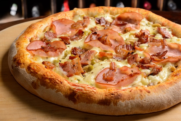 Entrecote en baconpizza op een houten plank braziliaanse pizza