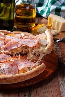 Entrecotepizza op braziliaanse wijze met mozzarella, palmharten en maïs. stuk wordt eruit gehaald en de kaas uitgerekt
