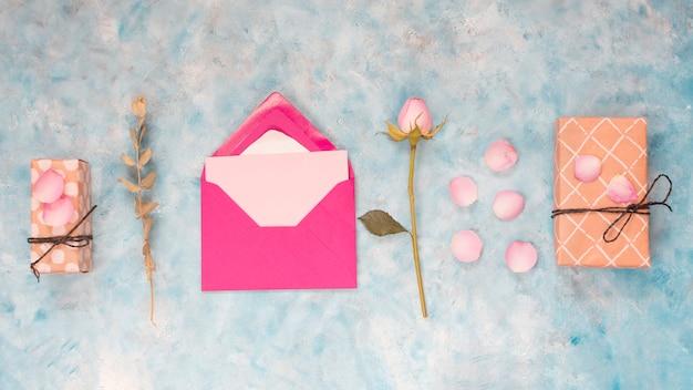 Envelop dichtbij huidige dozen, bloem en bloemblaadjes