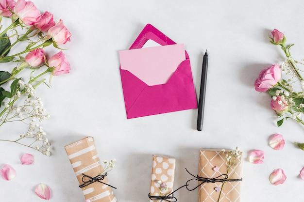 Envelop dichtbij pen, verse prachtige rozen en cadeaus