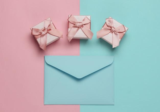 Envelop, dozen met geschenken op roze blauwe pastel achtergrond. kerstmis, valentijnsdag, bruiloft of verjaardag. bovenaanzicht