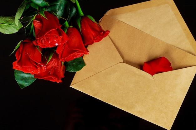 Envelop en boeket van rode rozen op zwarte tafel. valentijnsdag concept.