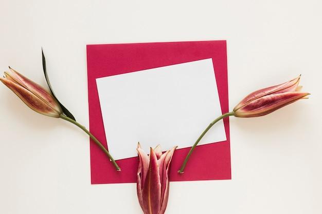 Envelop en papier met koninklijke lelies bovenaanzicht