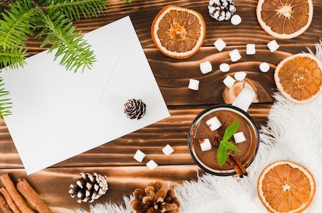 Envelop in de buurt van warme chocolademelk, sinaasappelen en marshmallow
