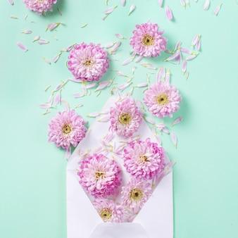 Envelop met bloemen en bloemblaadjes op een pastelroze