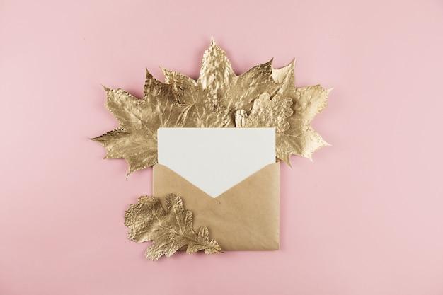 Envelop met brief en glanzende gouden marmerblaadjes op roze, plat leggen