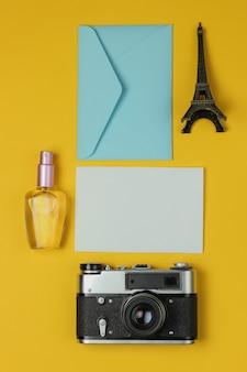 Envelop met brief, retro camera en schoonheidstoebehoren op gele achtergrond. bovenaanzicht. reis concept. kopieer ruimte