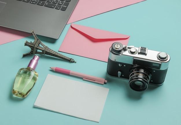 Envelop met brief, retro camera, laptop en beautyaccessoires op roze blauwe pastel achtergrond. bovenaanzicht. reis concept.