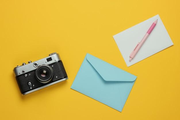 Envelop met brief, retro camera op gele achtergrond. bovenaanzicht. reis concept
