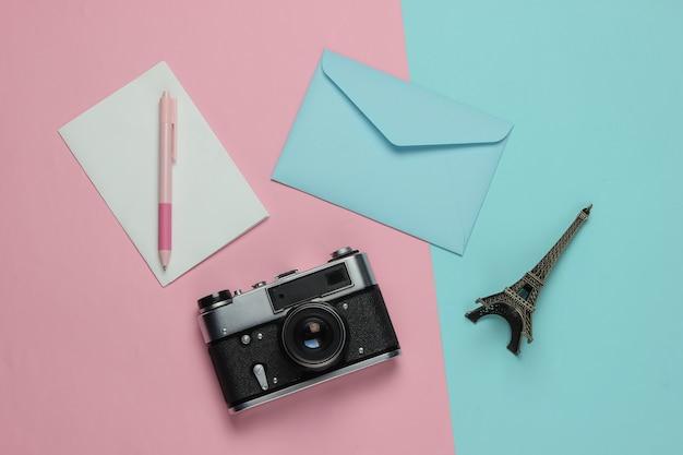 Envelop met brief, retro camera op roze blauwe pastel achtergrond. bovenaanzicht. reis concept. parijs reis