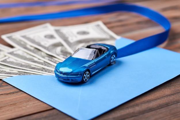 Envelop met dollars en lint. blauwe envelop in de buurt van plastic auto. lange harde weg naar rijkdom.