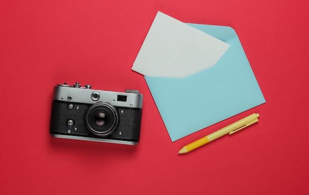 Envelop met een brief, retro camera op rode achtergrond. bovenaanzicht. reis concept