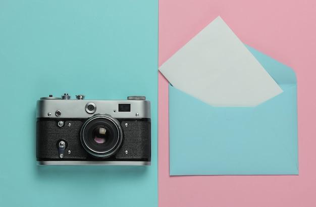 Envelop met een brief, retro camera op roze blauwe pastel achtergrond. bovenaanzicht. reis concept