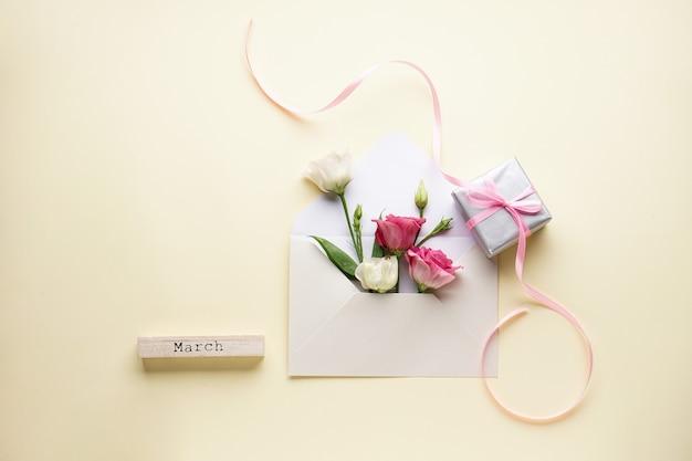 Envelop met eustomas, houten inscriptie - maart, met een geschenkdoos. plat leggen. 8 maart, vrouwendagkaart.