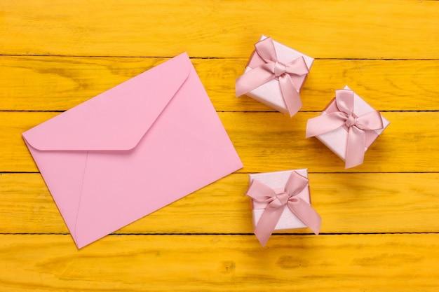 Envelop met geschenkdozen op gele houten