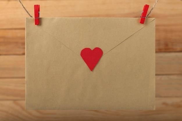 Envelop met hart hangend met wasknijpers aan touwkoordpin. brief voor dierbaren. valentijnsdag.