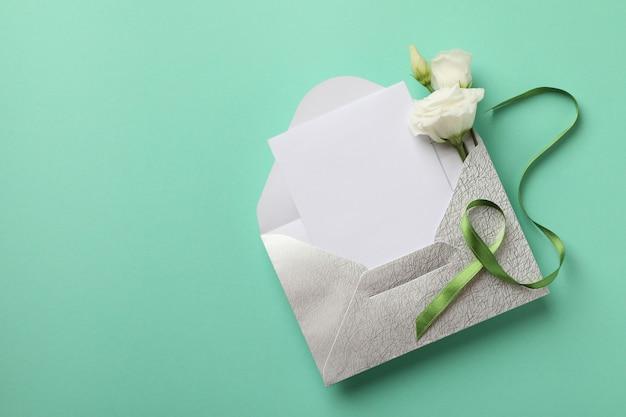 Envelop met lege kaart, rozen en groen lint op muntachtergrond