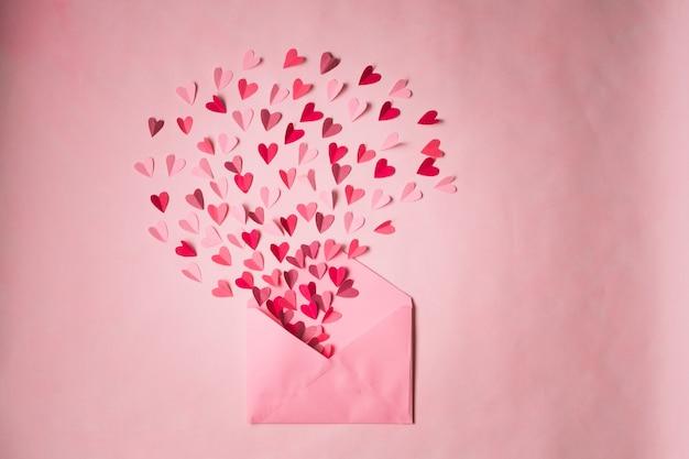 Envelop met papieren hartjes op een roze achtergrond. harten stijgen van binnenuit open envelop. romantische liefdesbrief.