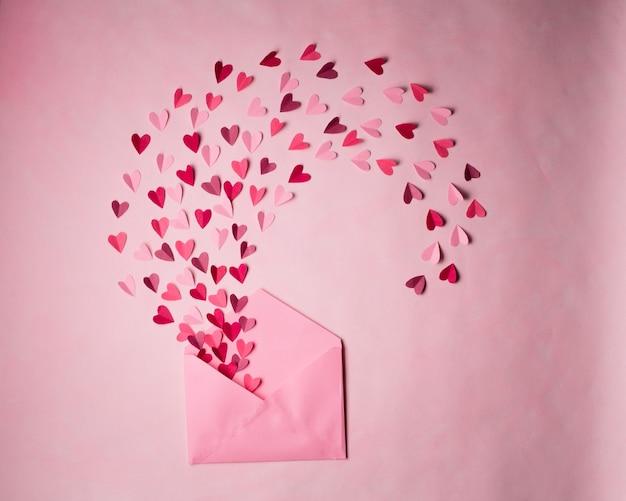 Envelop met papieren hartjes op roze