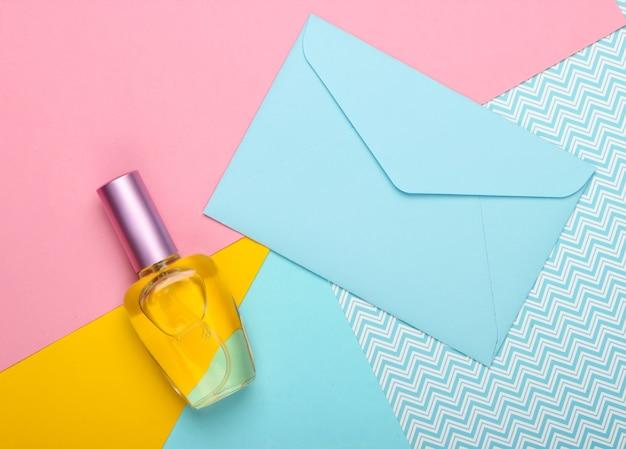 Envelop met romantische brief en parfumflesje op een pastel achtergrond. bovenaanzicht