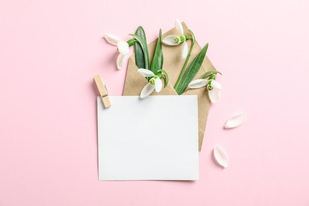 Envelop met sneeuwklokjebloemen en document op kleurenachtergrond