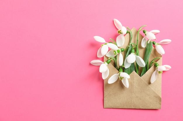 Envelop met sneeuwklokjebloemen op kleurenachtergrond, ruimte voor tekst