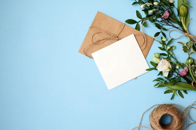 Envelop, papieren kaart en bloemen op blauwe achtergrond.