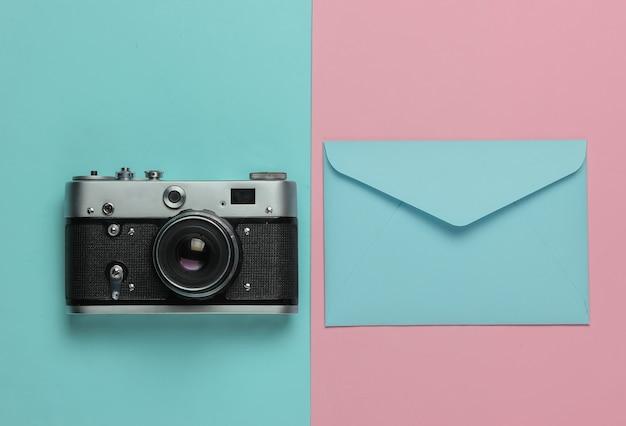 Envelop, retro camera op roze blauwe pastel achtergrond. bovenaanzicht. reis concept