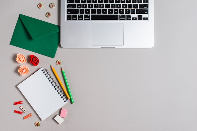 Envelop; rozen; kleurpotloden; spiraal blocnote en laptop op grijze achtergrond