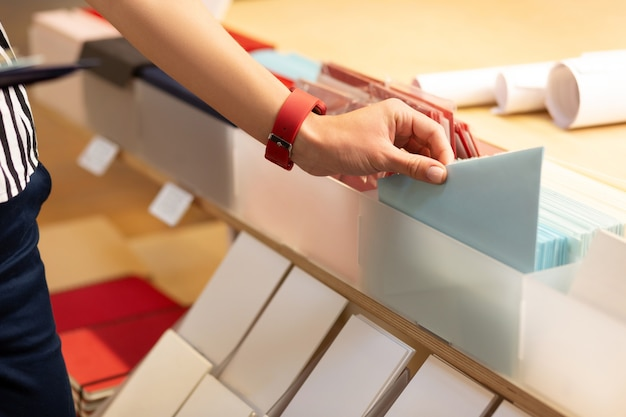 Enveloppen leggen. vrouw die gestreepte blouse draagt die in kantoorboekhandel werkt die enveloppen zet