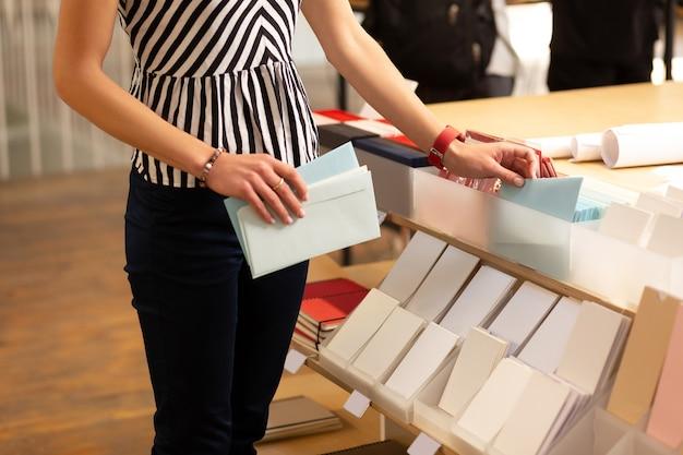 Enveloppen leggen. winkelbediende van kantoorboekhandel druk bezig met het op orde brengen van enveloppen