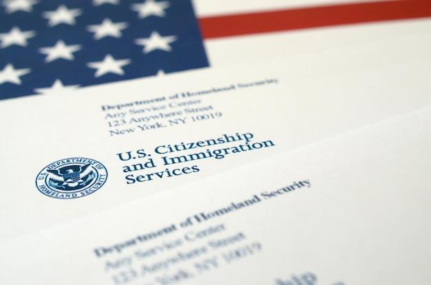 Enveloppen met brief van uscis op de vlag van de verenigde staten van het department of homeland security