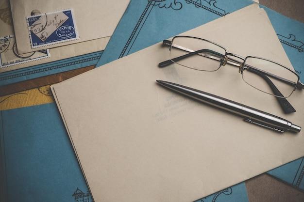Enveloppen met postzegels, pen, potloden, glazen zijn aan de oppervlakte. geel en blauw briefpapier. bovenaanzicht. vignet