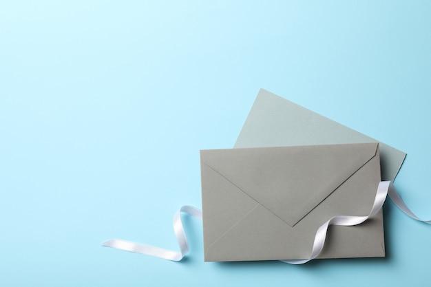 Enveloppen met wit krullend lint op blauwe achtergrond