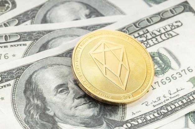 Eos-munt op dollarbankbiljetten. cryptocurrency op amerikaanse dollarbiljetten