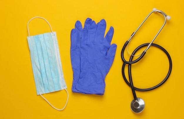 Epidemie. medische handschoenen en masker, stethoscoop op geel.