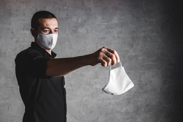 Epidemioloog die beschermend ademhalingsmasker aanbiedt in coronavirusconcept, selectieve aandacht