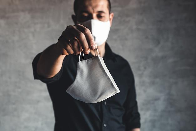 Epidemioloog die een ademhalingsmasker aanbiedt ter bescherming tegen coronavirus