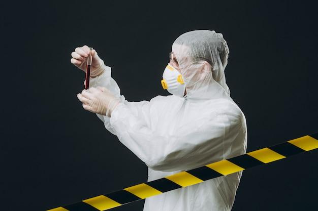 Epidemioloog over beschermende kleding met reageerbuis op een beperkt gebied