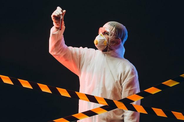 Epidemioloog over beschermende kleding op een beperkt gebied met een reageerbuis