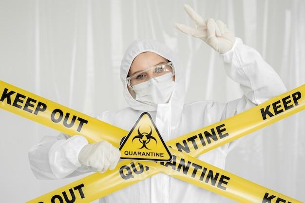 Epidemioloog vrouw in beschermende kleding bevindt zich in een verboden gebied met een gevaarsteken