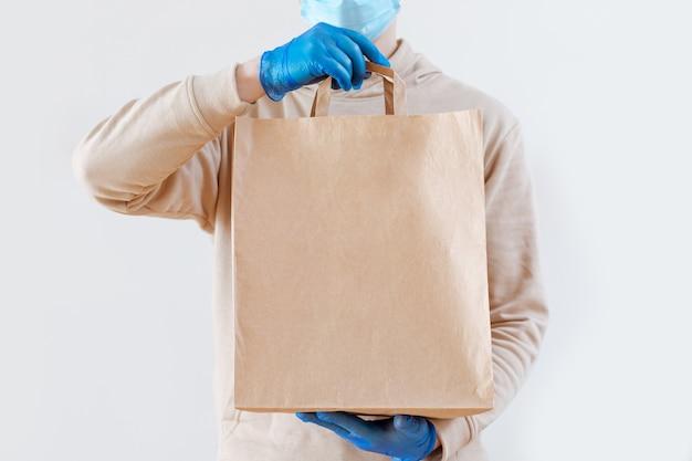 Epidemisch coronavirus. koffie, fastfood-pakket. contactloos eten bezorgen. een koerier in handschoenen en een masker houdt eco-verpakking vast. blijf thuis, blijf veilig