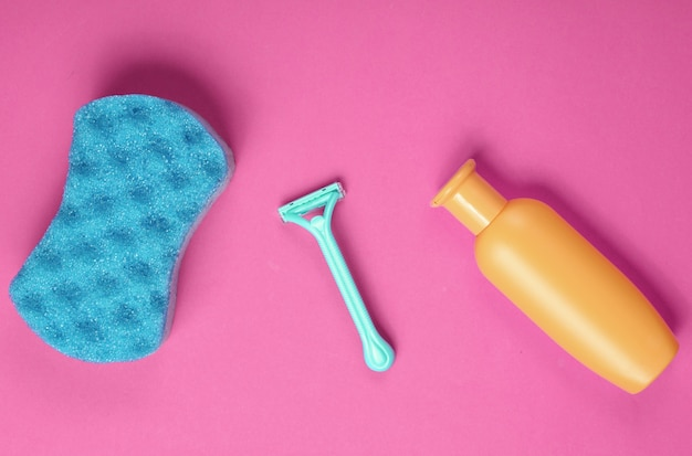 Epilator scheermes, spons, fles shampoo op roze achtergrond