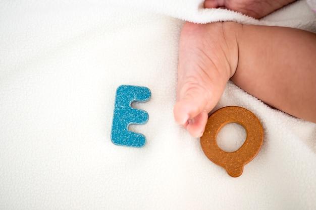 Eq-tekst houten woord op deken met vage jonge geitje voet en exemplaar ruimteachtergrond