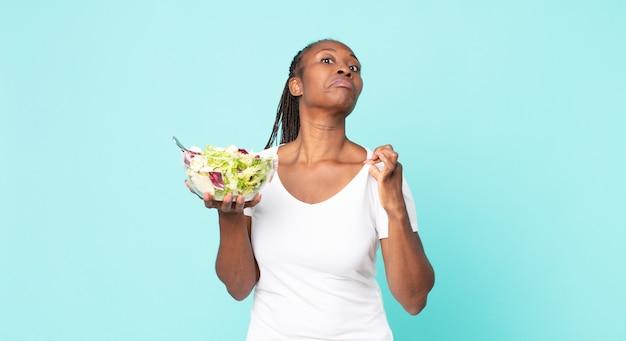 Er arrogant, succesvol, positief en trots uitzien en een salade vasthouden