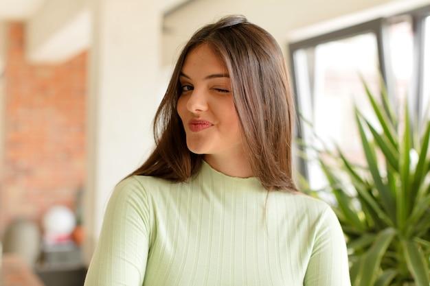 Er blij en vriendelijk uitzien, glimlachend en met een positieve houding naar je knipogen
